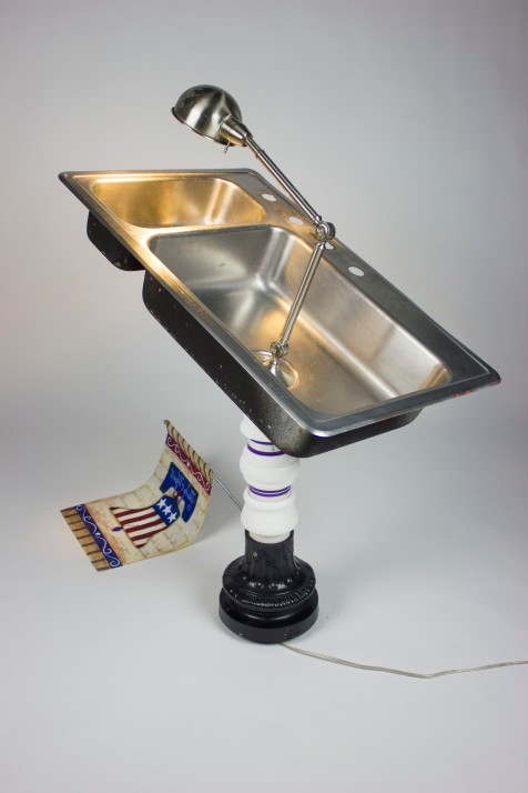 Made with found stainless steel sink, found desk lamp, found street light base, found garden flag, PVC pipe, lathed cast plastic, threaded rod, steel, and mixed media