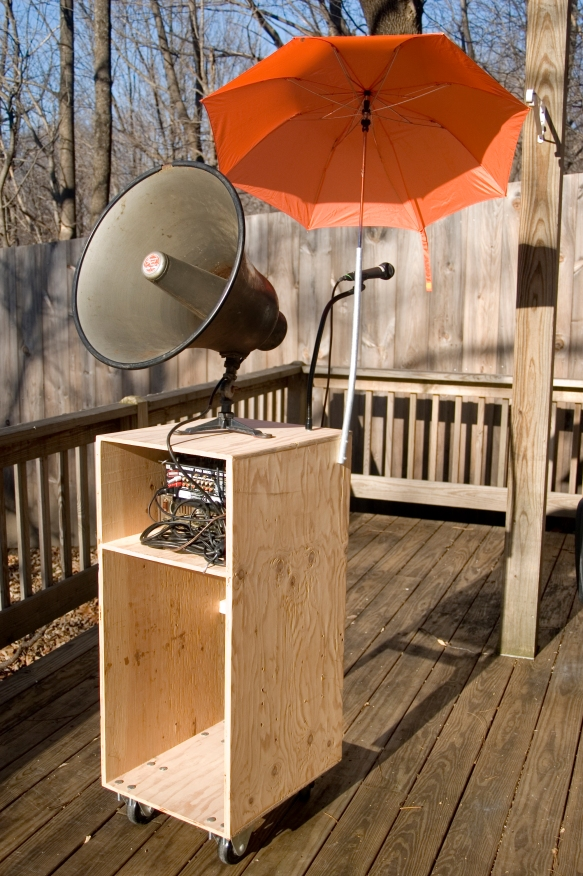 Performance cart complete with PA speaker, mixer, microphone, umbrella, and hookups to source power